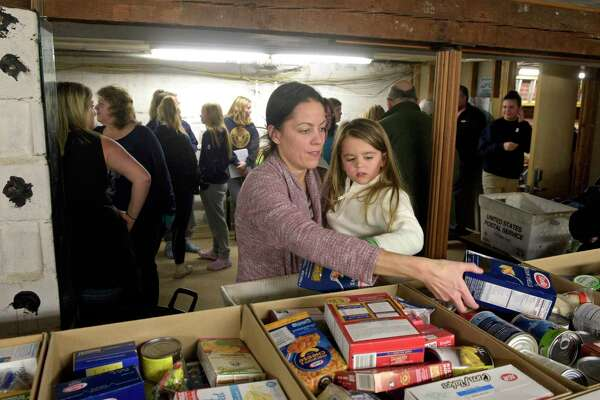 Kim Rissolo, of Bethel, and her daughter Chloe, 3, volunteered at Brotherhood in Action, a Bethel based food pantry, to pack boxes of food to be delivered to families in need. The pantry expects to give food to 140 families. Wednesday night, November 20, 2019, in Bethel, Conn.