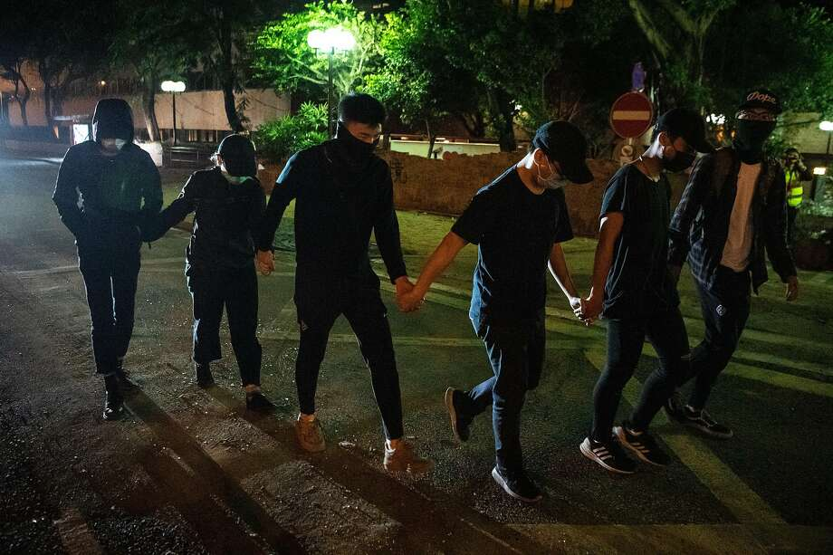 Anti-government protesters hold hands while leaving the campus of Hong Kong Polytechnic University to surrender to police. Photo: Laurel Chor / Getty Images