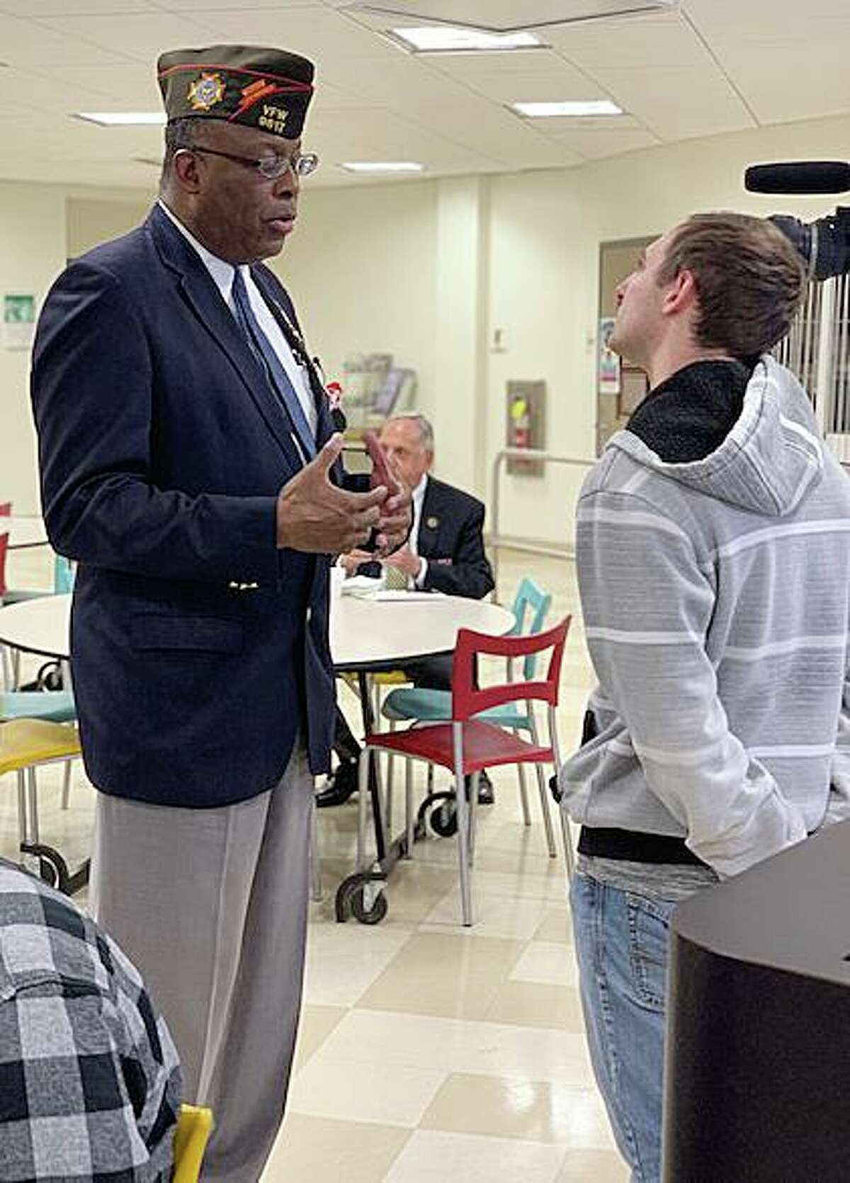 Veteran Archie Elam speaks with a camerman from News 12 at the Academy of Information Technology & Engineering's 12th annual Veterans Day Breakfast on Nov. 7, 2019 in Stamford, Conn.
