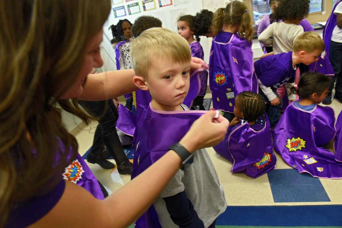 Kristen Buyce puts a cape on Jacob Kuba, 4, after her daughters explained epilepsy with a slide show to the pre-school class at New Scotland Elementary School on Friday, Nov. 22, 2019 in Albany, N.Y. Her daughter Nova, 4, has epilepsy. (Lori Van Buren/Times Union)