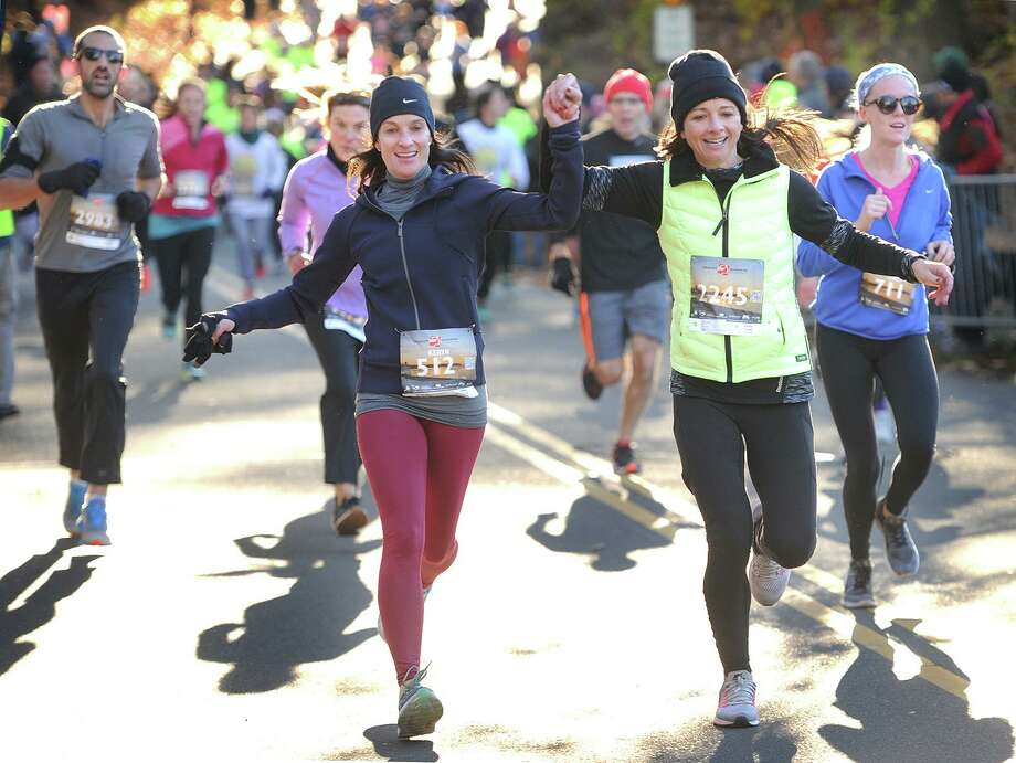 Friends Keryn Geller, left, of Westport, and Kristy Gordon, of Weston, grasp hands as the cross the finish line at the annual Pequot Runners 5-mile Thanksgiving Day Road Race in the Southport section of Fairfield, Conn. on Thursday, November 23, 2017. Over 4000 runners registered for this year's race. Photo: Brian A. Pounds / Hearst Connecticut Media / Connecticut Post