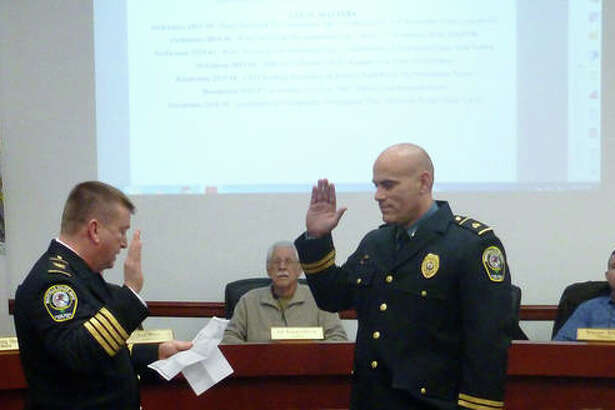 Maryville Chief of Police Rob Carpenter, left, swears in his new deputy chief, Tony Manley, during Wednesday's village trustee board meeting. In the background are the mayor and various trustees.