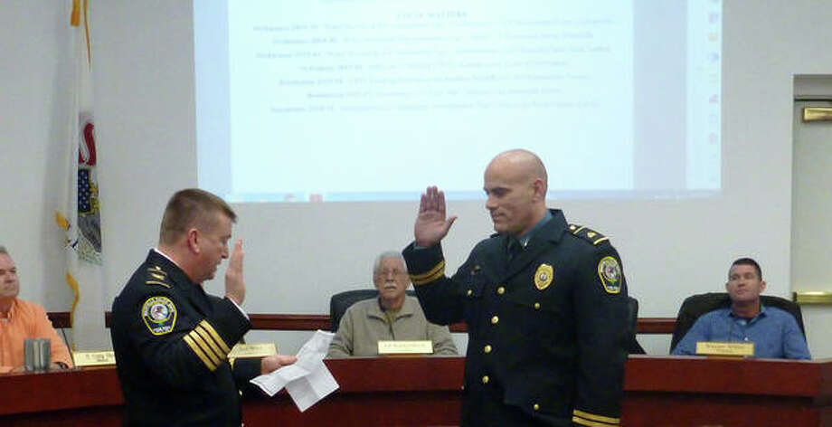 Maryville Chief of Police Rob Carpenter, left, swears in his new deputy chief, Tony Manley, during Wednesday's village trustee board meeting. In the background are the mayor and various trustees. Photo: Courtesy Of Maryville Police Department