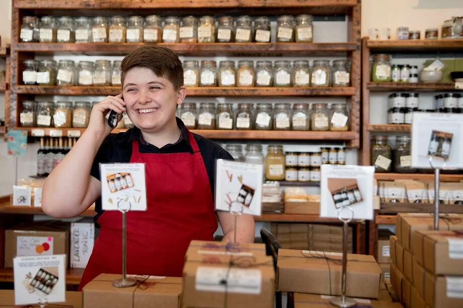 Evan Murphree Gamble, who uses they/them pronouns, chats on the phone with a customer while working at Oaktown Spice Shop in Oakland. Photo: Jessica Christian / The Chronicle
