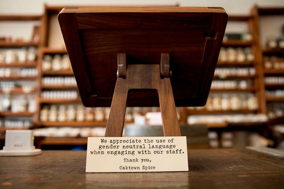 A sign is posted on the cash register at Oaktown Spice Shop in Oakland asking customers to use gender-neutral language with employees. Photo: Jessica Christian / The Chronicle