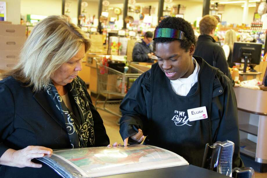 State Sen. Mary Daugherty Abrams, left, visits with Elijah, a worker at Meriden's Big Y. Here, he shows Abrams his art portfolio. Photo: Contributed Photo