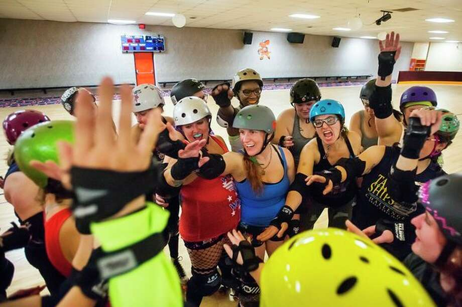 "Members of the Chemical City Derby Girls, along with participants of the team's ""fresh meat training camp,"" huddle up and cheer at the end of a practice session Oct. 7 at the Roll Arena in Midland. (Katy Kildee/kkildee@mdn.net)"