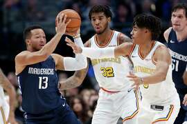 Dallas Mavericks guard Jalen Brunson (13) looks to make a pass as Golden State Warriors' Marquese Chriss (32) and Jordan Poole, right, defend in the first half of an NBA basketball game in Dallas, Wednesday, Nov. 20, 2019.