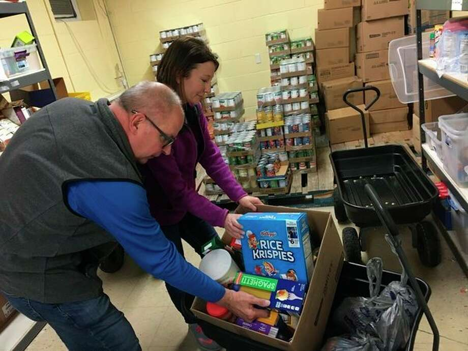 Project Starburst volunteers, pictured from left, Bob King and Meranda Babb, are shown filling a box with donations. (Courtesy photo)