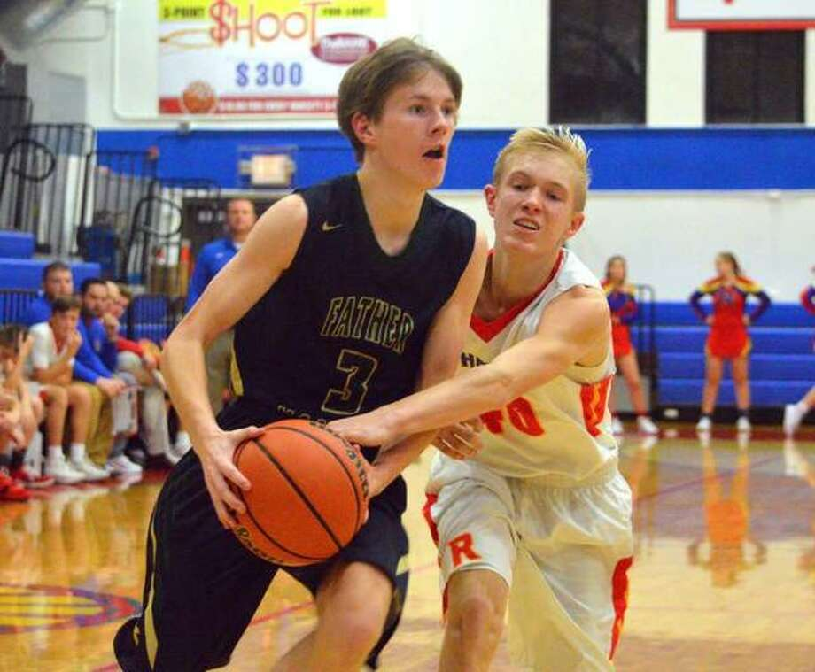 Father McGivney's Kellen Weir, left, drives to the basket during a game at Roxana last season. Photo: Scott Marion/The Intelligencer