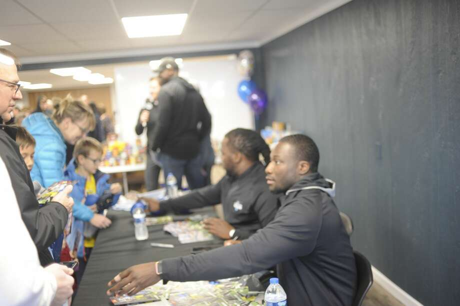 Former University of Michigan quarterback Devin Gardner, foreground, and former Detroit Lions running back Joique Bell, center, greet fans and sign autographs while spending two hours Friday afternoon at the Midland County Emergency Food Pantry Network during a food drive there. As part of Football Week in Michigan, Gardner, Bell and former Lions receiver Herman Moore were also scheduled to spend an hour at the Midland Kroger later in the day to promote Kroger's Zero Hunger Zero Waste initiative. Fox Sports Detroit and Ford are also partnering in this endeavor. Photo: Dan Chalk/chalk@mdn.net