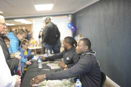 Former University of Michigan quarterback Devin Gardner, foreground, and former Detroit Lions running back Joique Bell, center, greet fans and sign autographs while spending two hours Friday afternoon at the Midland County Emergency Food Pantry Network during a food drive there. As part of Football Week in Michigan, Gardner, Bell and former Lions receiver Herman Moore were also scheduled to spend an hour at the Midland Kroger later in the day to promote Kroger's Zero Hunger Zero Waste initiative. Fox Sports Detroit and Ford are also partnering in this endeavor.