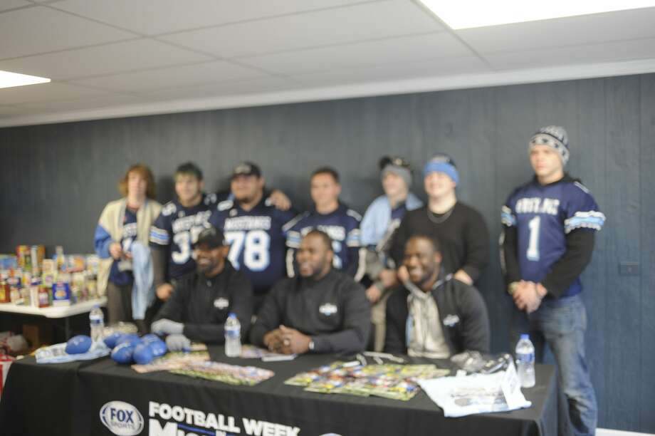 A group of students poses for a photo with former Detroit Lions receiver Herman Moore (seated, left), former Lions running back Joique Bell (center) and former Michigan quarterback Devin Gardner (right). The three athletes were at the Midland County Emergency Food Pantry on Friday afternoon to meet the public and to promote food drives both at the food pantry and at Kroger later that day. Photo: Dan Chalk/chalk@mdn.net