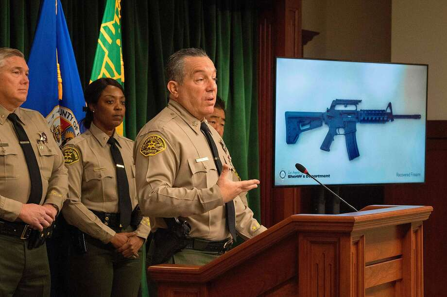 Los Angeles County Sheriff Alex Villanueva stands beside an image of the rifle deputies seized at the home of the 13-year-old boy who allegedly threatened to carry out a school shooting. Photo: Mark Ralston / AFP Via Getty Images