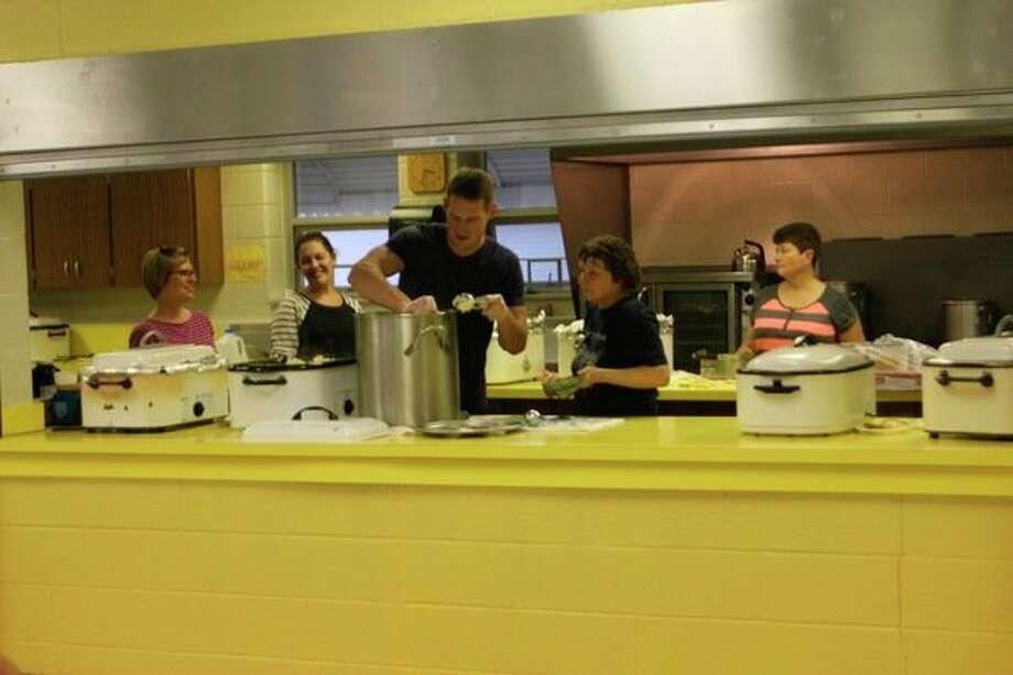 Cody Ney and other volunteers work to mash potatoes.(Sara Eisinger/Huron Daily Tribune)