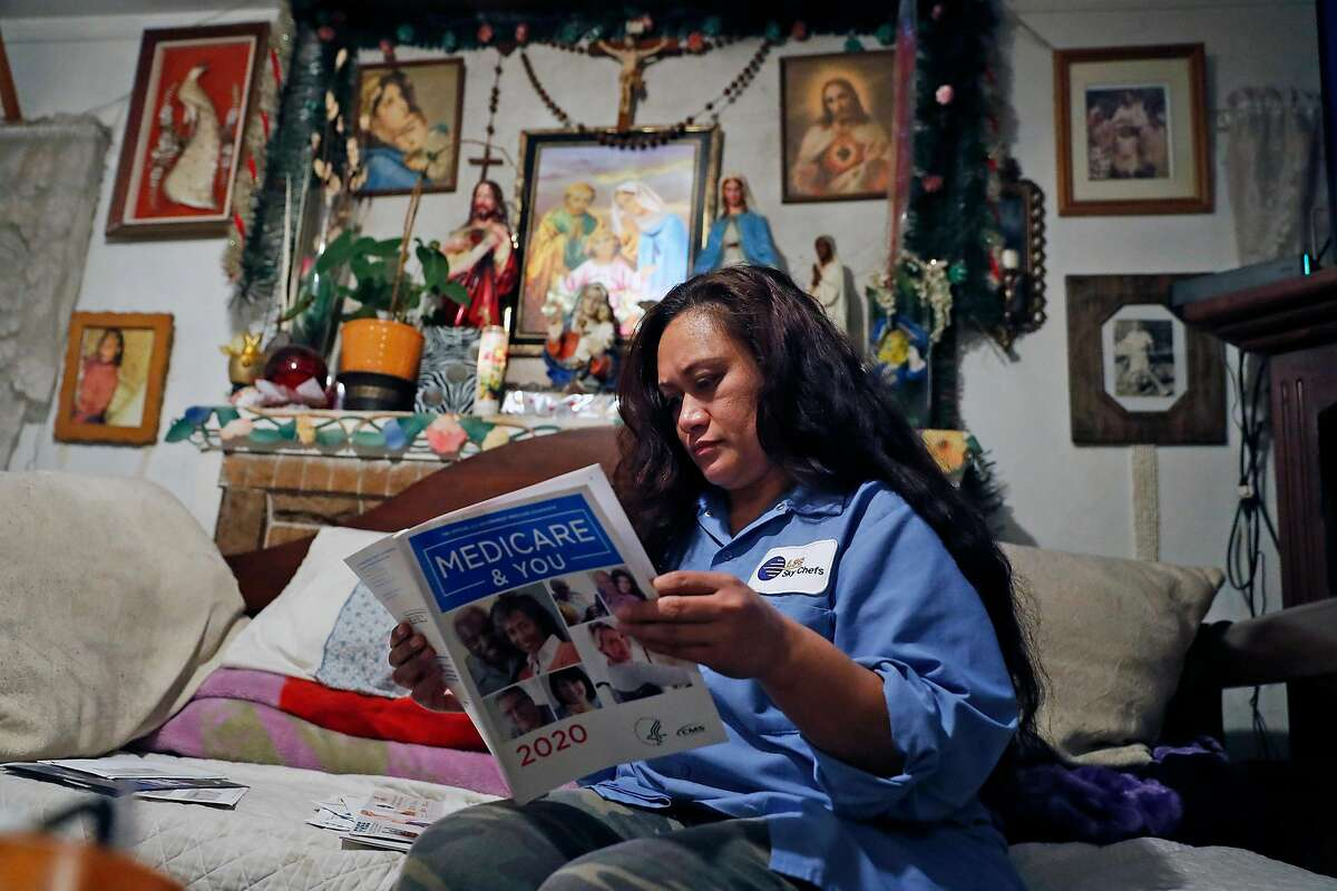 While going through the mail, LSG Sky Chefs' employee Melieni Cruz looks through her mother's Medicare brochure at her home in Oakland, Calif., on Monday, November 18, 2019.