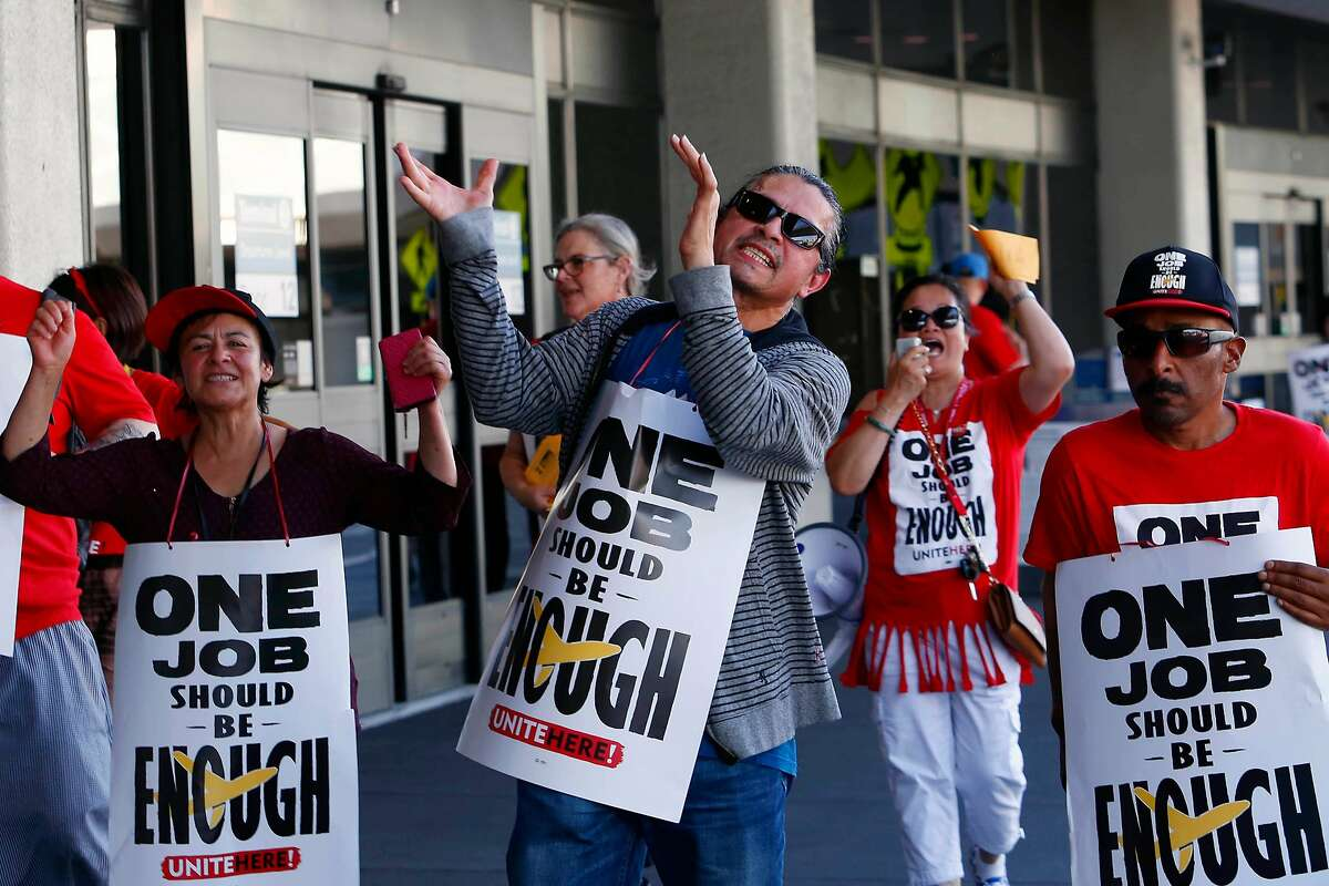 Nathanel Baquedano (front with hands raised clapping) cheers and pickets with other Unite Here members and supporters at Terminal 3 at San Francisco International Airport on Wednesday, September 25, 2019 in San Francisco, CA.