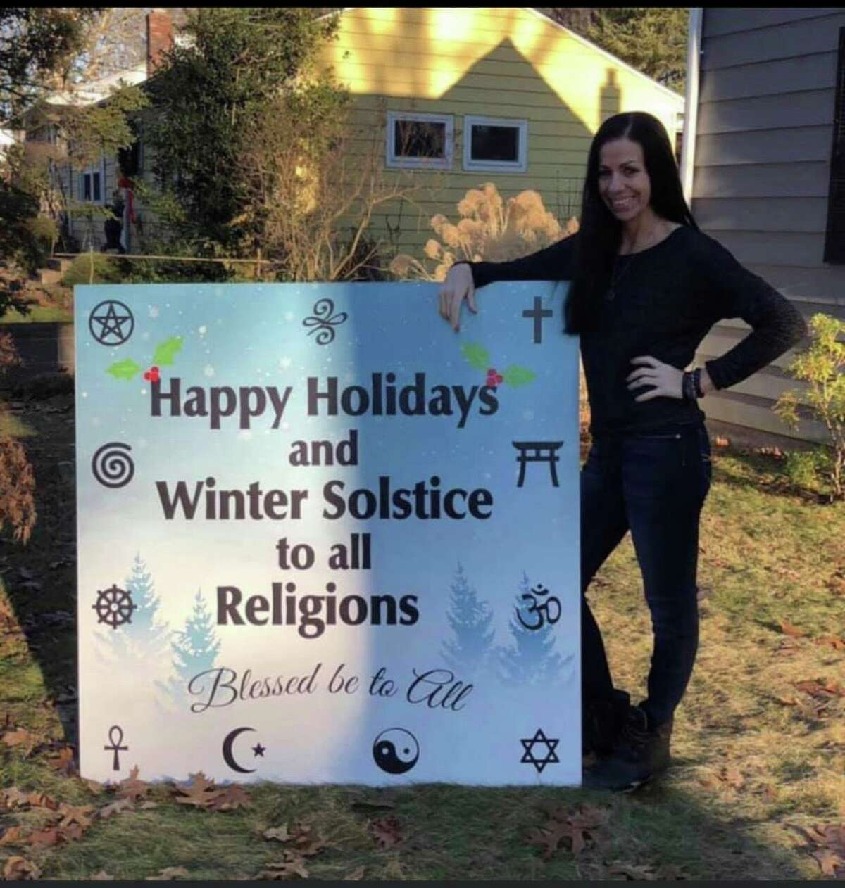 East Havener Michelle Piercey, who practices witchcraft, with the holiday sign she recently was approved to place on the East Haven Green. The sign will be unveiled on Dec. 1 at 1 p.m.