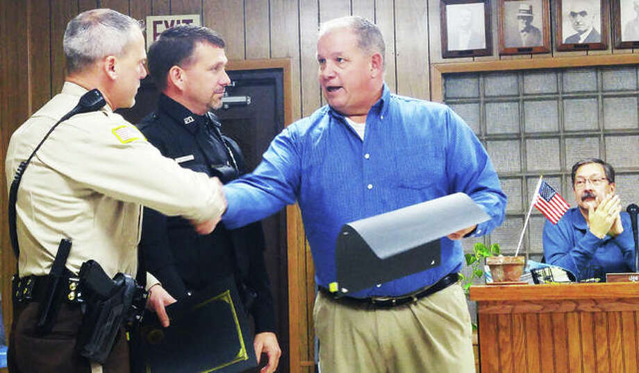 Grafton Mayor Rick Eberlin, right, presents certificates of appreciation to Jersey County Deputy Justin Decker, left, and Grafton Police Officer Mike Angel during the village's Nov 19 council meeting. The two officers were honored for their outstanding performance during a Grafton fire where they quickly evacuated residents and minimized property loss. Photo: Jeanie Stephens|The Telegraph