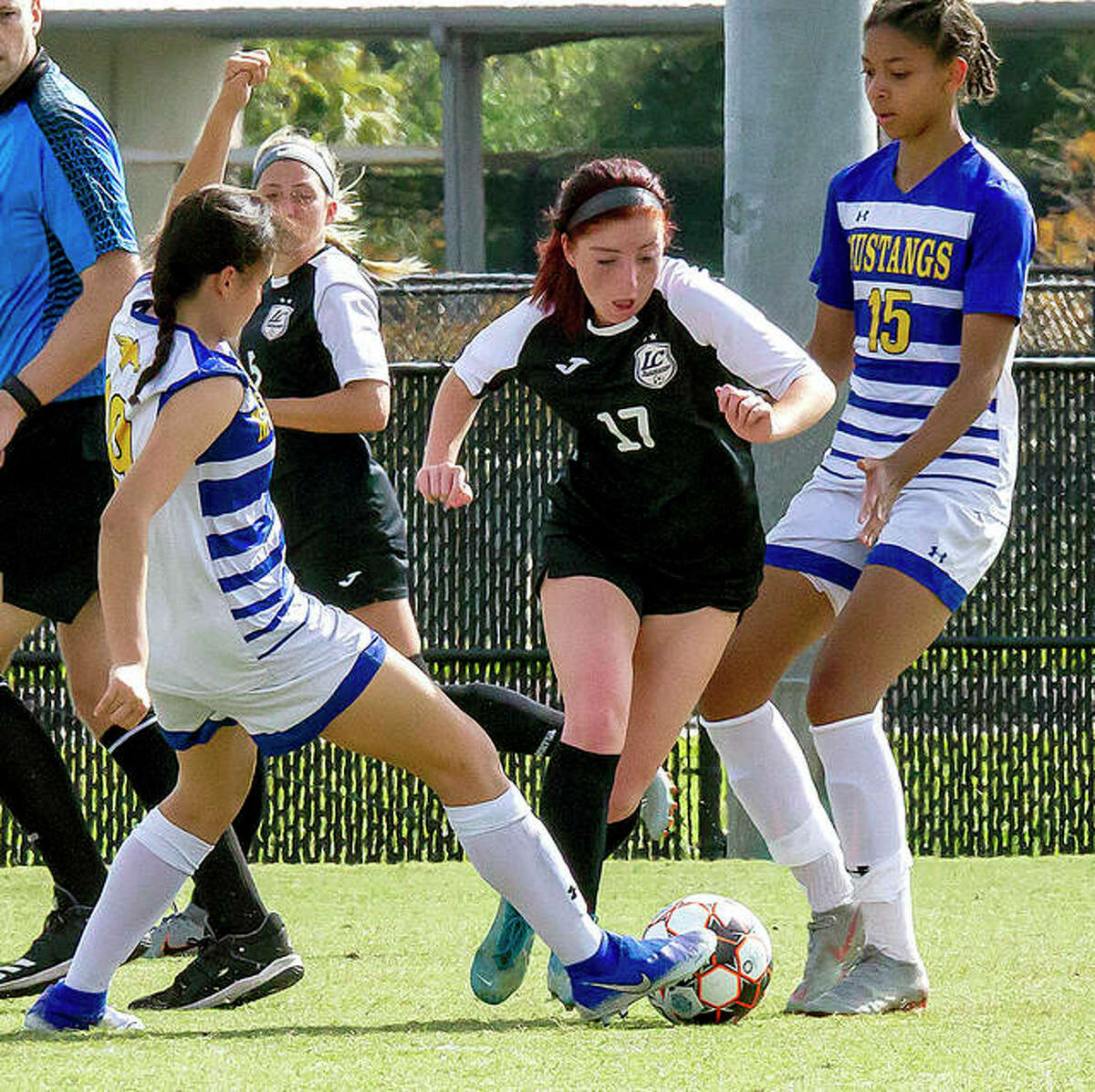 Lewis and Clark's Ella Kiely (17) moves the ball between Monroe players Alexandra Sandoval, left, and Regina Fiabema in the second half of Friday's NJCAA National Tournament semifinal game in Melbourne, Fla.