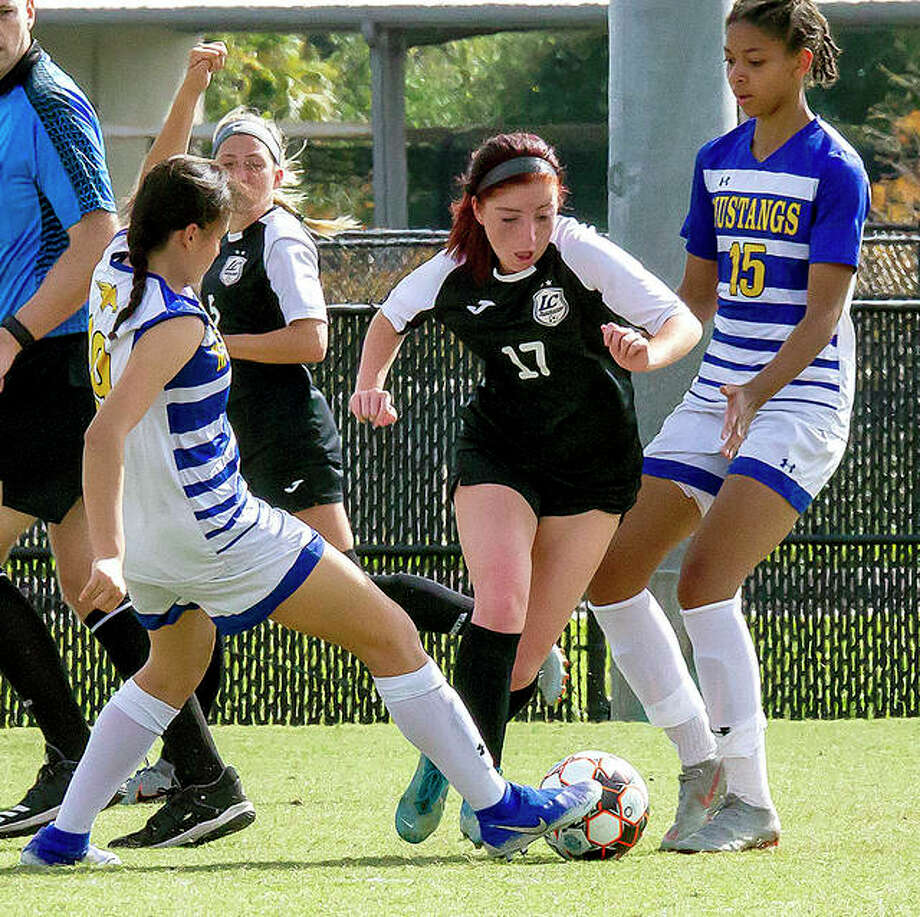 Lewis and Clark's Ella Kiely (17) moves the ball between Monroe players Alexandra Sandoval, left, and Regina Fiabema in the second half of Friday's NJCAA National Tournament semifinal game in Melbourne, Fla. Photo: Jan Dona | For The Telegraph