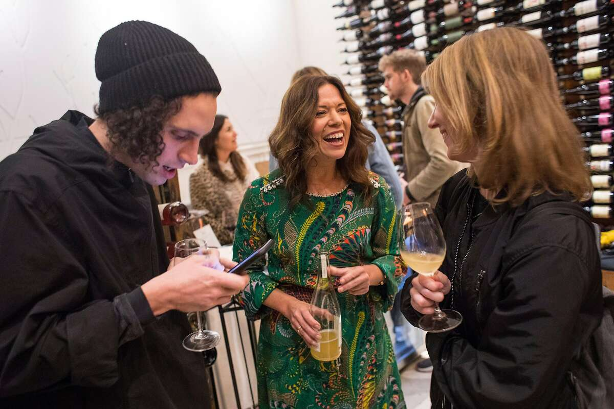 Owner of Biondivino wine shop Ceri Smith, center, pours a bottle-fermented sparkling wine for Marco Tarantelli, left, and Rachel Spackman during a wine tasting at the shop on Tuesday, Nov. 19, 2019 in San Francisco, Calif.