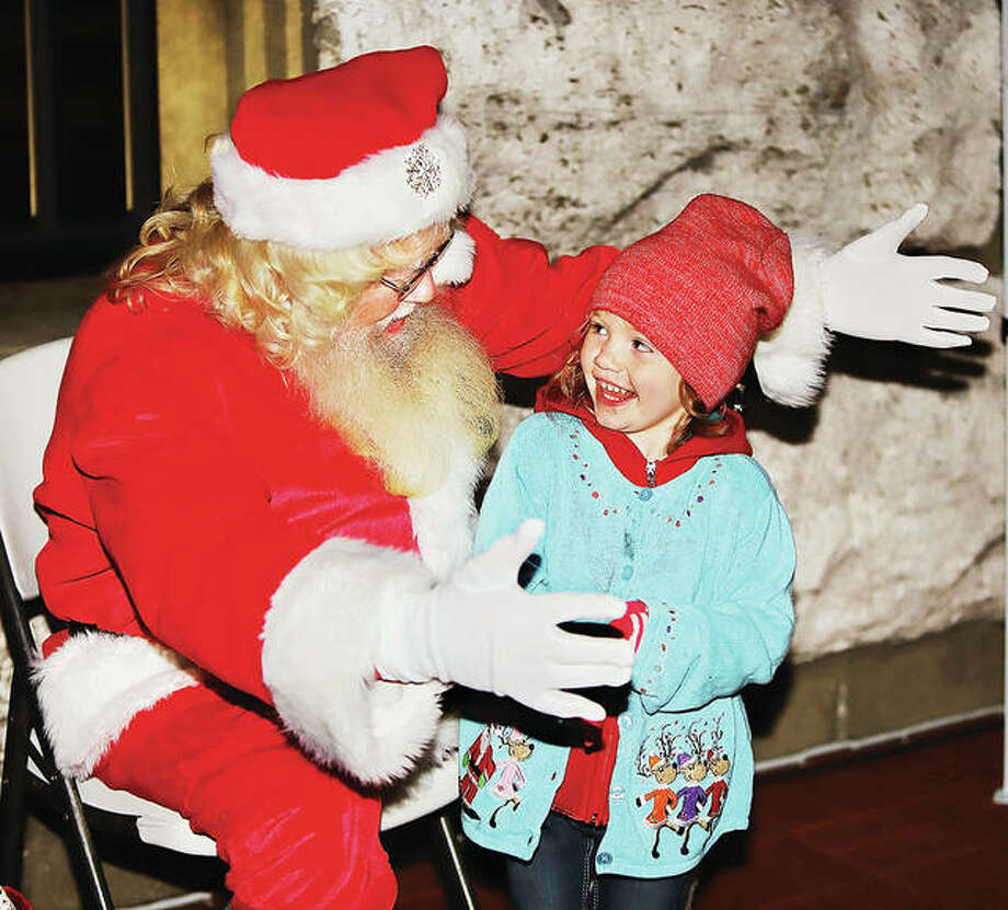 Santa Claus holds out his arms to give a big welcome and hug to Alayna Ahlin, 3, of Jerseyville, as she meets him Friday night at the 25th Annual Community Tree Lighting in Lincoln-Douglas Square in Alton. Several hundred people showed up to see Santa, listen to Christmas carols and see the downtown tree lit.