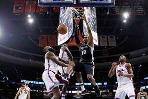San Antonio Spurs' LaMarcus Aldridge, right, hangs from the rim after a dunk next to Philadelphia 76ers' James Ennis III, center, and Kyle O'Quinn, front left, during the first half of an NBA basketball game Friday, Nov. 22, 2019, in Philadelphia. (AP Photo/Matt Slocum)