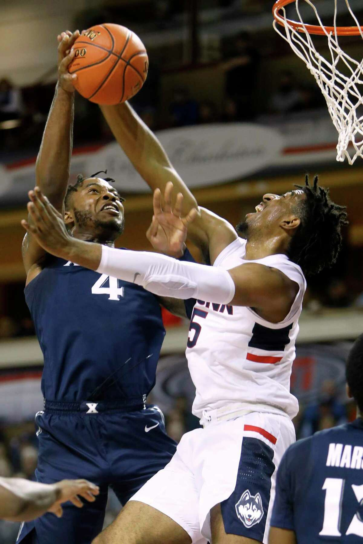 Xavier's Tyrique Jones, at left, goes up for a shot against the defense of Connecticut's Isaiah Whaley in the first half of an NCAA college basketball game during the Charleston Classic Friday, Nov. 22, 2019, in Charleston, SC. (AP Photo/Mic Smith)