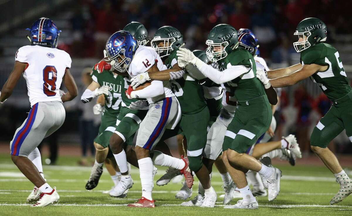 West Brook Bruins wide receiver Thaddeaus Johnson (12) is gang tackled by Strake Jesuit Crusaders defense in the first quarter of high school playoff football game on November 22, 2019 at Challenger Stadium in Waller, TX.