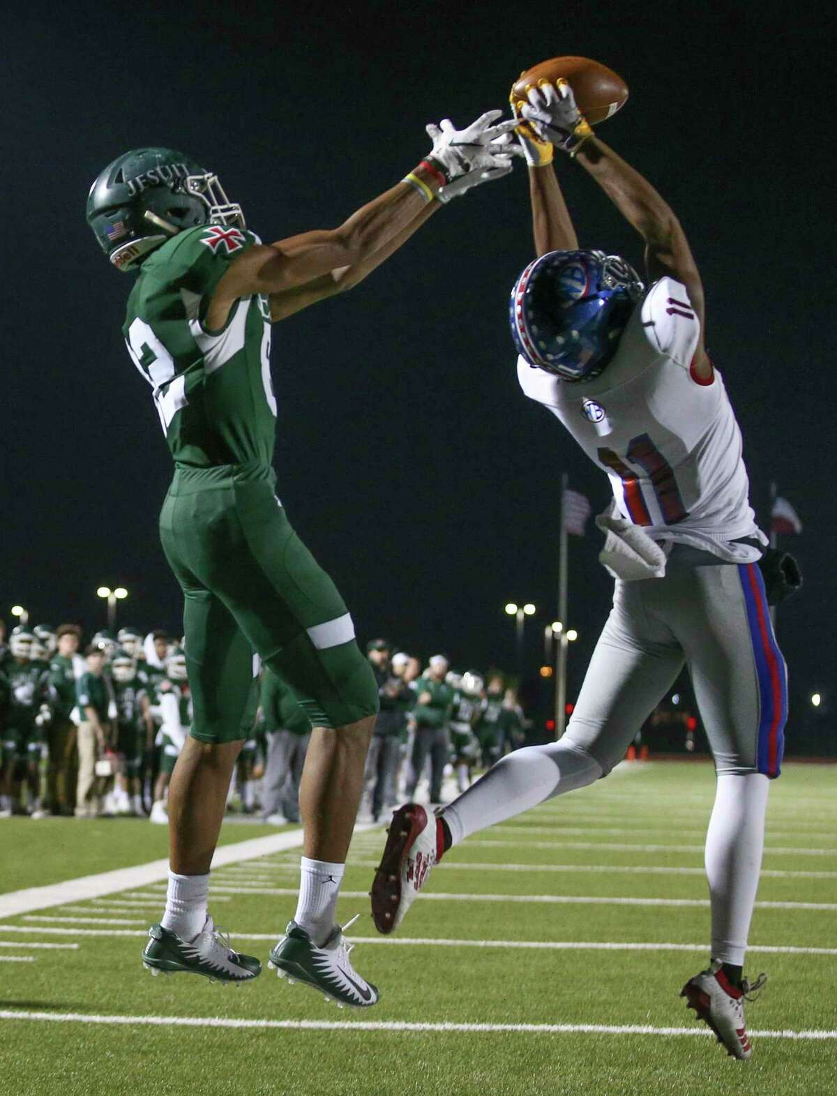 West Brook Bruins safety Bryce Anderson (11) intercepts the ball against Strake Jesuit Crusaders wide receiver Thaddeaus Johnson (12) in the first quarter of high school playoff football game on November 22, 2019 at Challenger Stadium in Waller, TX. The play was over turned because of pass interference on Anderson.