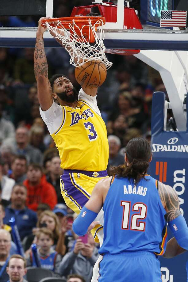 Lakers forward Anthony Davis dunks for two of his 33 points in his team's win over host Oklahoma City. Photo: Sue Ogrocki / Associated Press