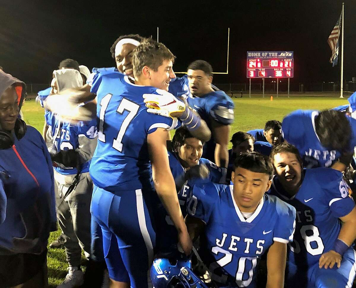 Encinal placekicker John Brindley (17) is hugged by teammate Vincent Nunley after Brindley's 23-yard field goal at the end of regulation lifted the Jets to a 24-21 win.