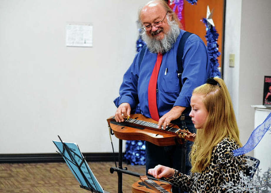Lauryn Maher (right) plays the dulcimer with Mike Anderson Friday during the Festival of Trees at Pathways Services.