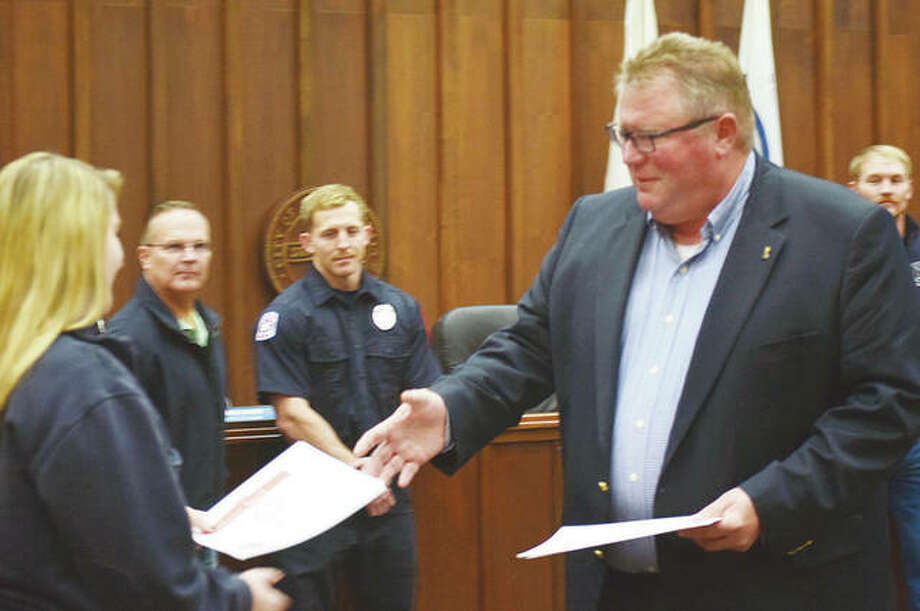Mayor Andy Ezard presents Allie Taberski of West Central Joint Dispatch with a certificate Friday for being part of a team that quickly helped Joseph Keen when the Jacksonville resident went into sudden cardiac arrest in September. Photo: Marco Cartolano | Journal-Courier