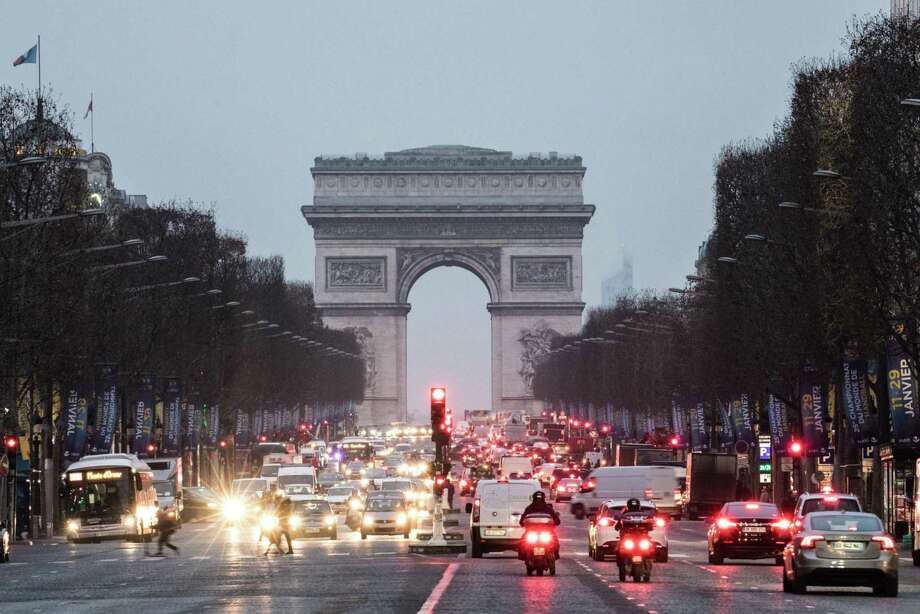 Vehicles sit at traffic lights as the Arc de Triomphe stands beyond in Paris on Jan. 25, 2017. Photo: Bloomberg Photo By Christophe Morin. / © 2017 Bloomberg Finance LP