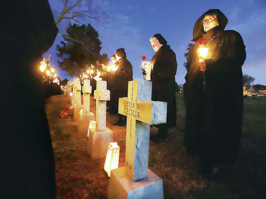 Sisters stand in front of the graves of nuns from the Sisters of St. Francis of the Martyr St. George in Alton Friday evening to lay roses on the graves as part of a celebration of the order's 150th year. Founded in 1869, the group's American Province began in St. Louis in 1923 before moving to Alton two years later.
