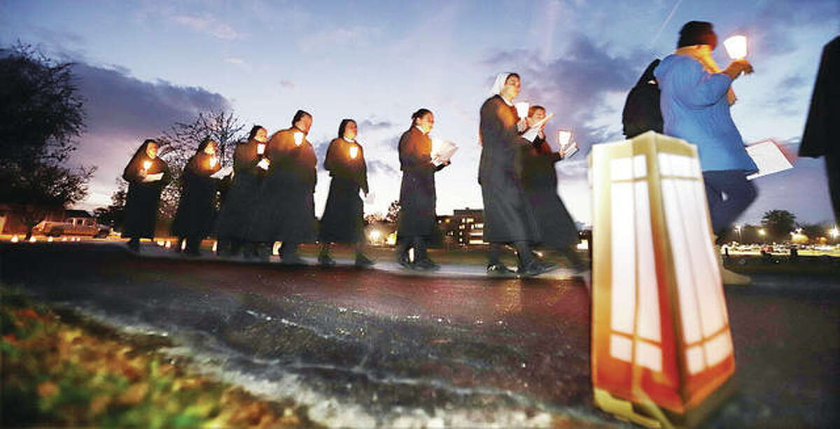 Sisters make the walk from their nearby convent, adjacent to OSF St. Anthony's Medical Center, to St. Joseph's Cemetery for the solemn ceremony Friday evening.