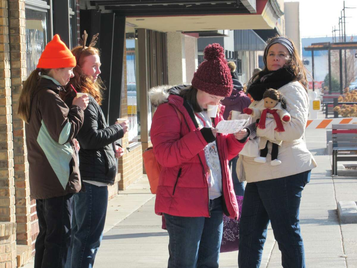 People visit downtown businesses and organizations during the Midland Downtown Business Association's Hot Cocoa Crawl on Saturday, Nov. 23.