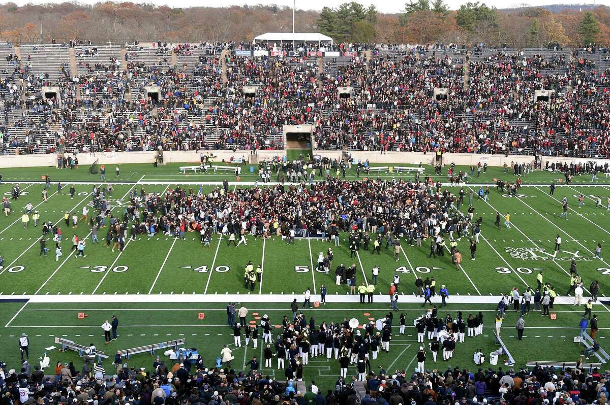 Fans stage a climate change protest at the Yale Bowl delaying the second half of the Yale/Harvard football game in New Haven, Connecticut, on November 23, 2019.