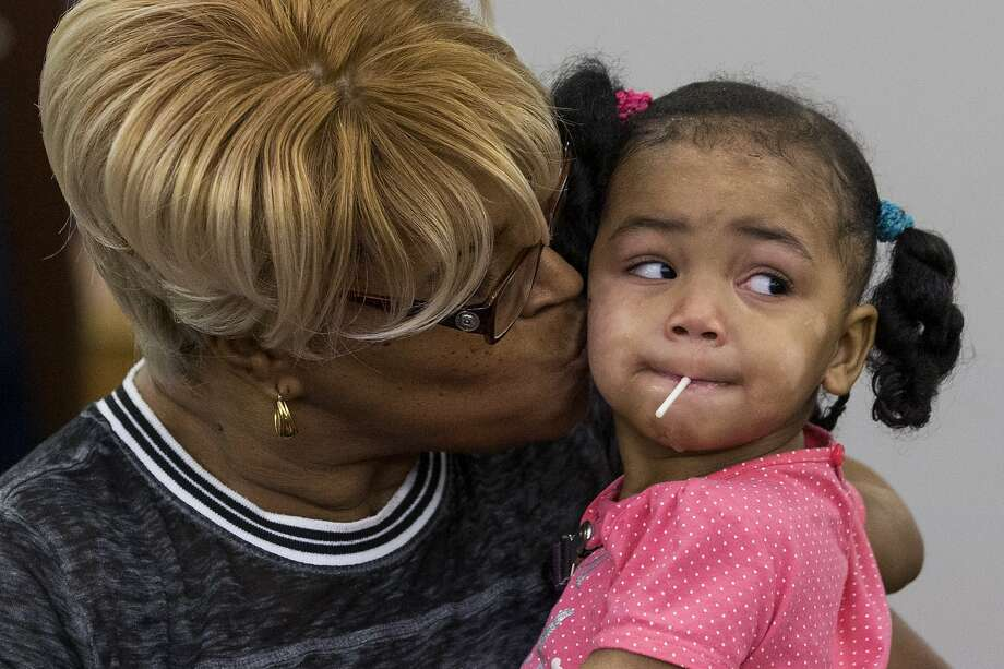 Felicia Simpson, left, kisses Kelci Lewis as she adopts young Kelci during the National Adoption Month ceremonies on Friday, Nov. 22, 2019, in Houston. The Texas Department of Family and Protective Services partnered with local courts and organizations to celebrate nearly two dozen families that became permanent. This past year, a record number of children found their forever homes across the state. Photo: Brett Coomer, Staff Photographer