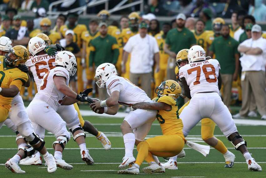 WACO, TEXAS - NOVEMBER 23: Sam Ehlinger #11 of the Texas Longhorns is sacked by Terrel Bernard #26 of the Baylor Bears in the first half at McLane Stadium on November 23, 2019 in Waco, Texas.