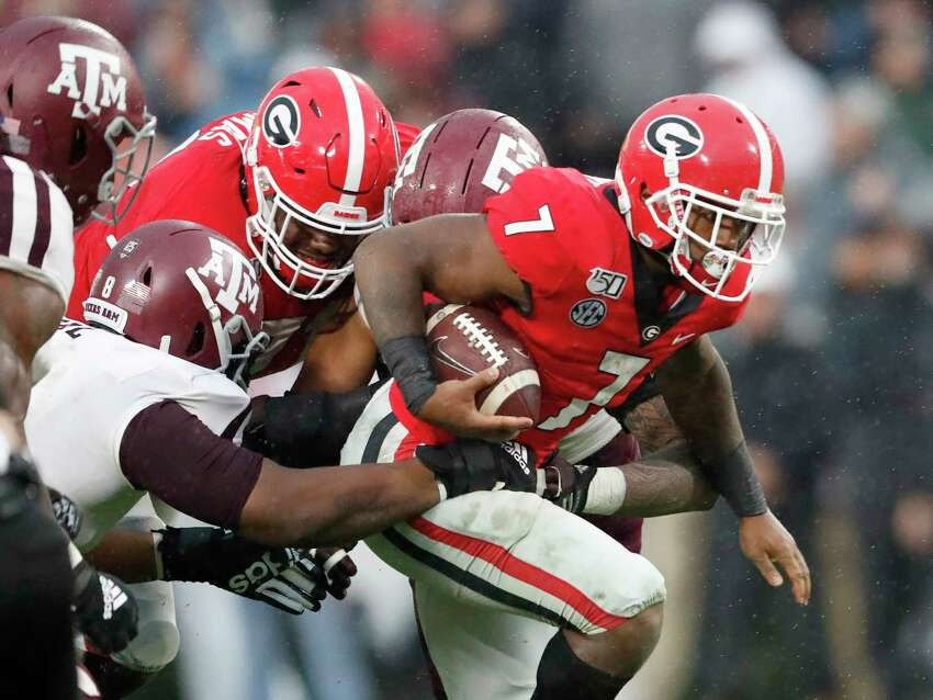Georgia running back D'Andre Swift (7) struggles for extra yardage against Texas A&M in the first half of an NCAA college football game Saturday, Nov. 23, 2019, in Athens, Ga. (AP Photo/John Bazemore)