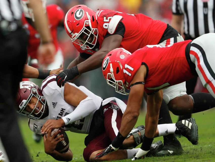 Texas A&M quarterback Kellen Mond (11) is sacked by Georgia defensive lineman Devonte Wyatt (95) and linebacker Jermaine Johnson (11) in the first half of an NCAA college football game Saturday, Nov. 23, 2019, in Athens, Ga. (AP Photo/John Bazemore)