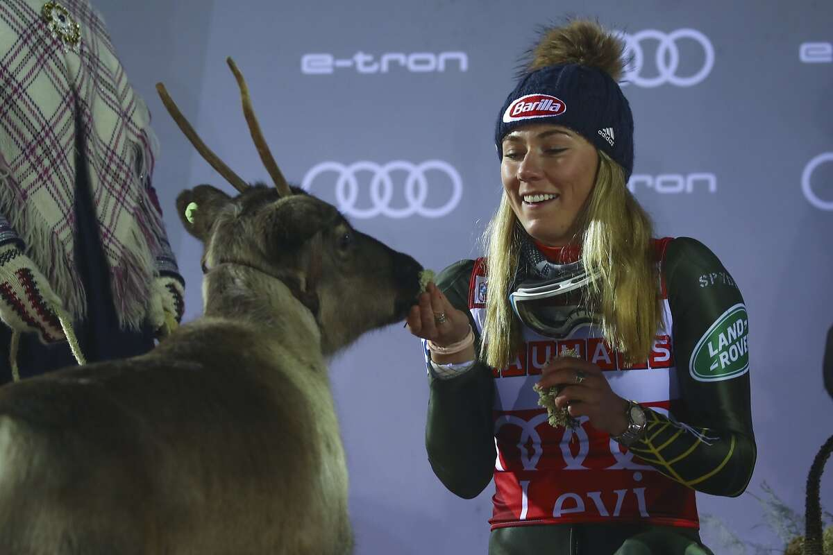 United States' Mikaela Shiffrin feeds a reindeer during the podium ceremony after winning an alpine ski, women's slalom in Levi, Finland, Saturday, Nov. 23, 2019. (AP Photo/Alessandro Trovati)