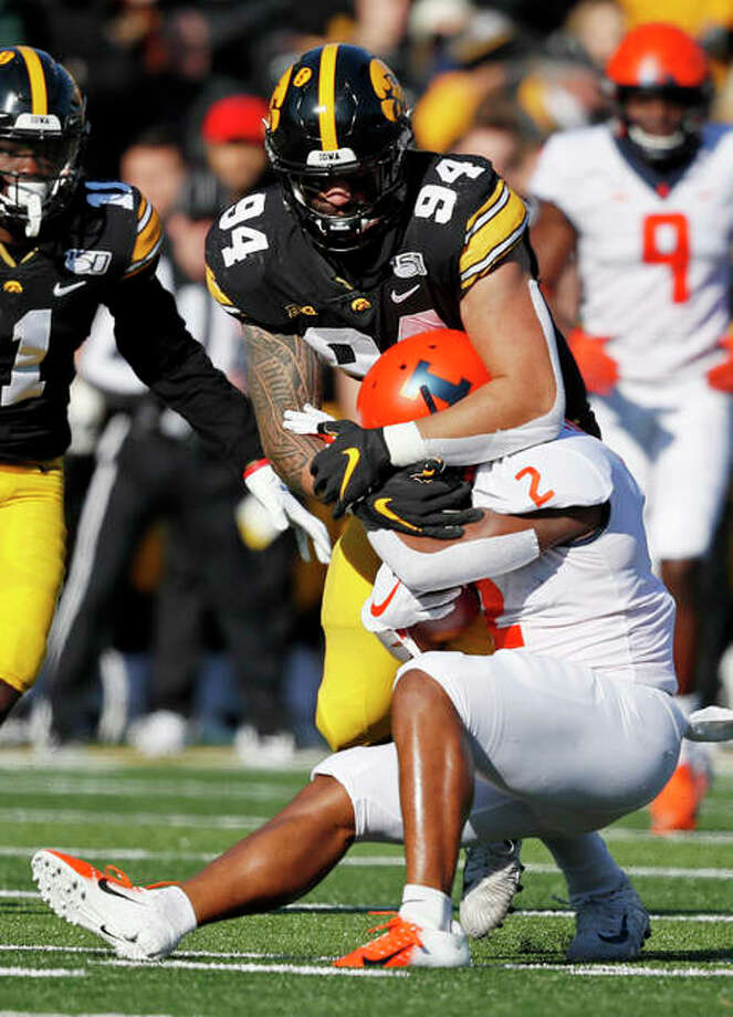 Illinois Reggie Corbin is tackled by Iowa defensive end A.J. Epenesa (94), a junior from Edwardsville, during the first half Saturday in Iowa City, Iowa. Photo: Associated Press