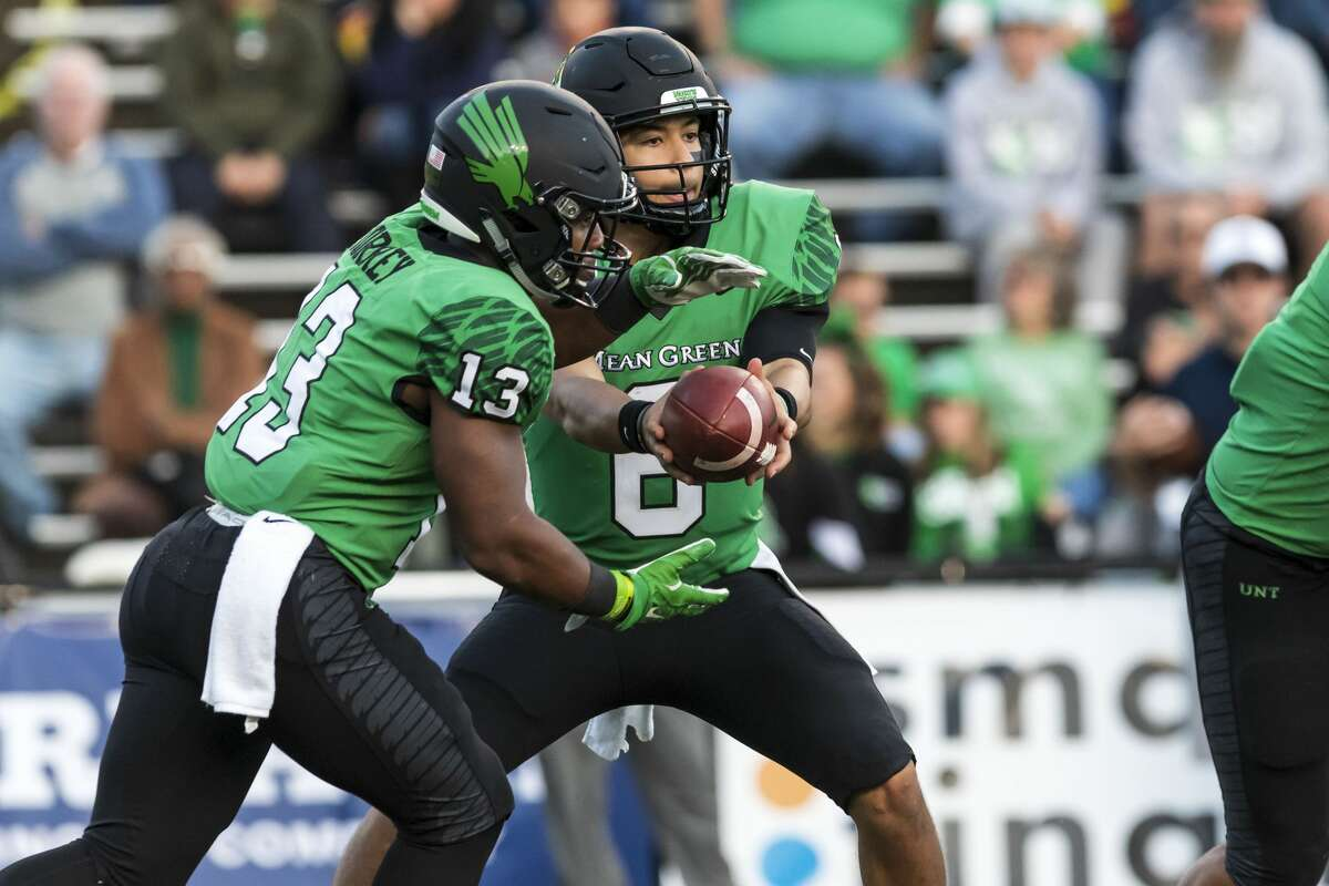 North Texas quarterback Mason Fine (6) hands the ball off to DeAndre Torrey (13) during the second half of college football game Saturday, Nov 23, 2019, in Houston.
