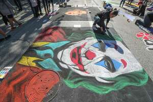 Alfredo Santillan works on his painting of The Joker during the 2019 Houston Via Colori, a street painting festival benefitting The Center for Hearing and Speech Saturday, Nov. 23, 2019, in Houston.