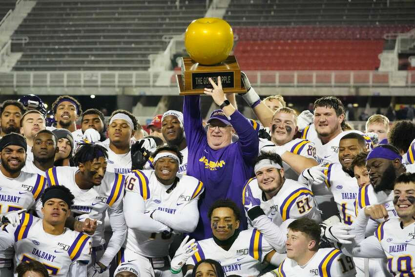 UAlbany coach Greg Gattuso and his players celebrate with the Golden Apple trophy after their 31-26 victory at Stony Brook on Saturday, Nov. 23, 2019. (Gregory A. Shemitz / Special to the Times Union)