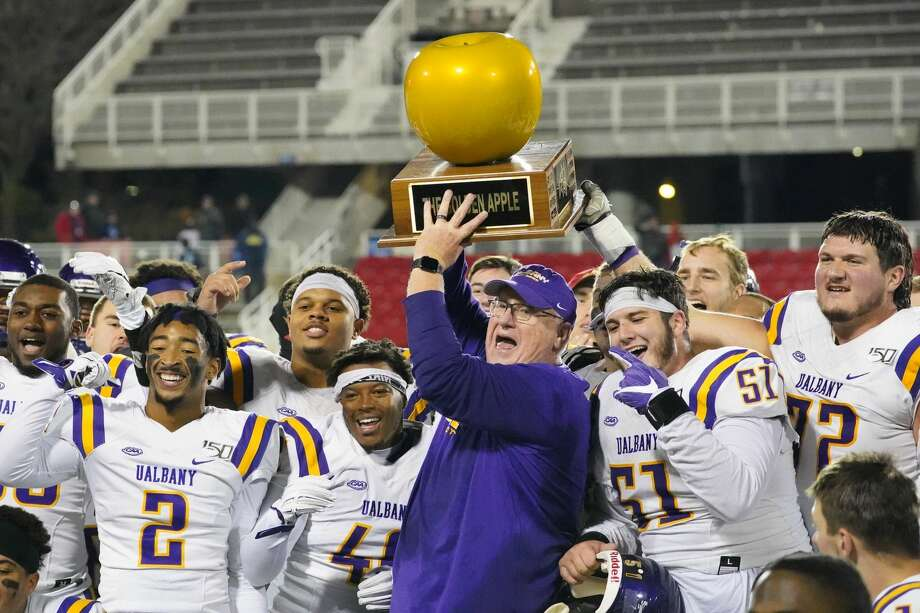 UAlbany coach Greg Gattuso and his players celebrate with the Golden Apple trophy after their 31-26 victory at Stony Brook on Saturday, Nov. 23, 2019. (Gregory A. Shemitz / Special to the Times Union) Photo: Gregory A. Shemitz / Special To The Times Union